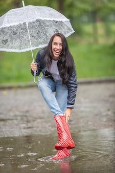 Vrouw lacht om water dat naar haar regenlaars lekt