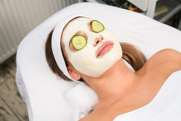 Vrouw lag op bank onder handdoek met wit alginaat professioneel peeling kleimasker