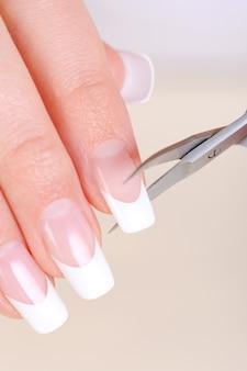 Vrouw lange nagels knippen op handen