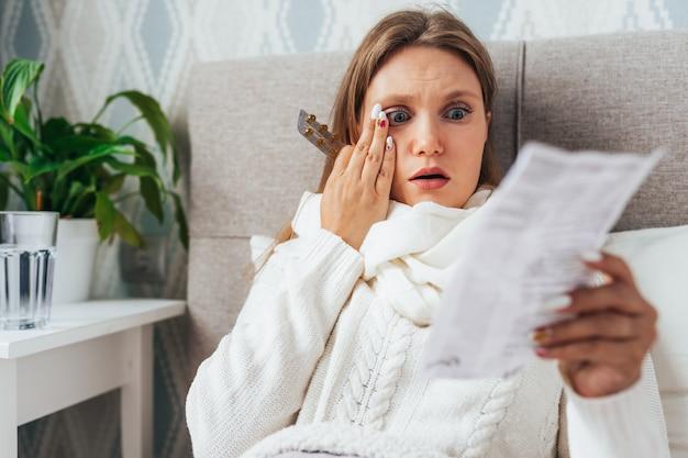 Vrouw las geneeskundefolder alvorens pillen in bed te nemen.