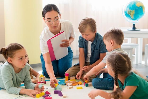 Vrouw leert kinderen een nieuw spel op de kleuterschool