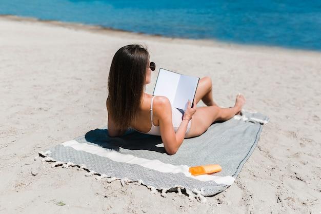 Vrouw leesboek in de buurt van water