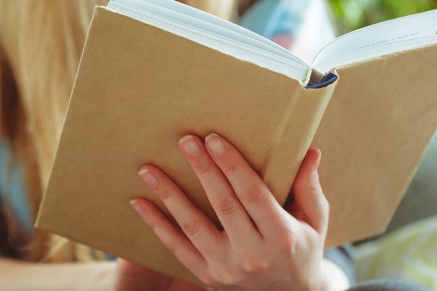 Vrouw leesboek in de kamer