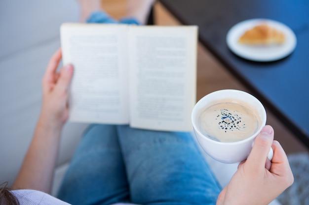 Vrouw leesboek met kopje koffie