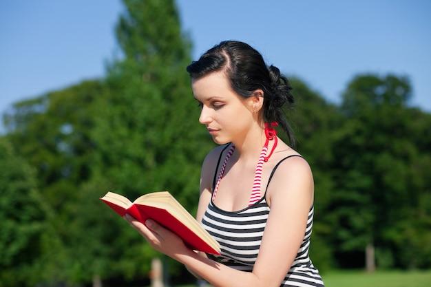 Vrouw leesboek op weide