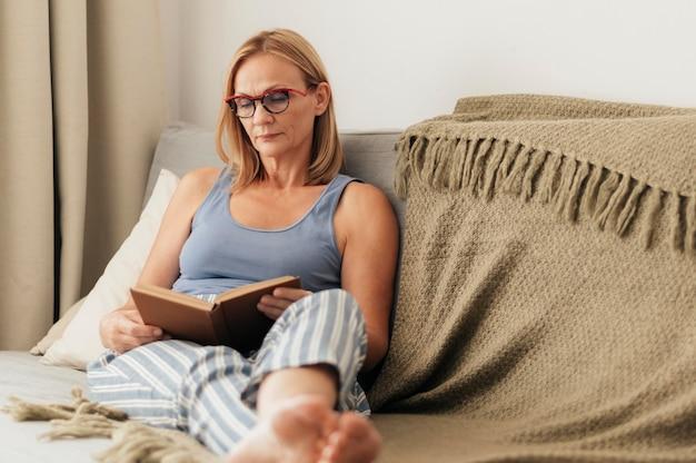 Vrouw leesboek thuis tijdens zelfisolatie