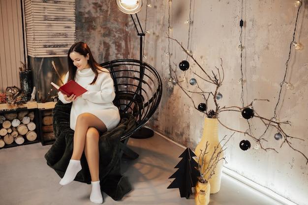 Vrouw leest boek bij de open haard zittend op de fauteuil.