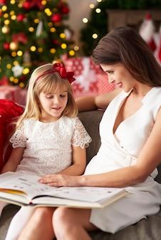 Vrouw leest boek met meisje