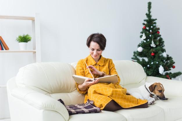 Vrouw leest boek voor kerstboom met hond jack russell terrier