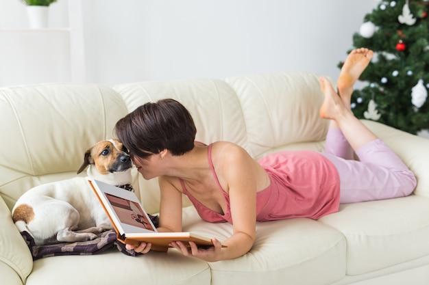 Vrouw leest boek voor kerstboom met hond