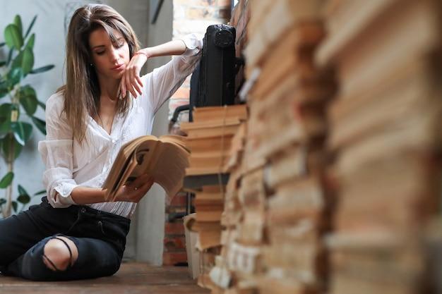 Vrouw leest boeken in de vloer