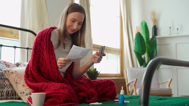 Vrouw leest de instructies van de pil, zittend op het bed bedekt met een deken