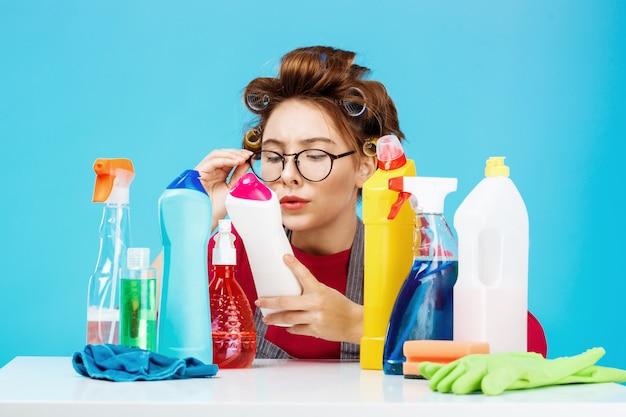 Vrouw leest details over fles terwijl ze huishoudelijk werk doet, ze ziet er moe uit