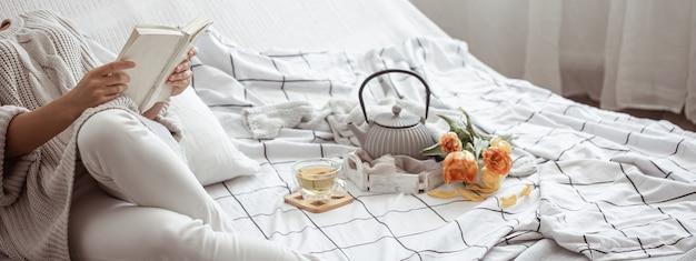 Vrouw leest een boek in bed met thee en boeket tulpen