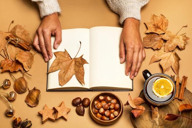 Vrouw leest een boek op een bruine tafel met een kopje thee in een bovenaanzicht