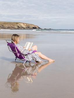 Vrouw leest een boek zittend op een stoel op het strand