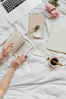 Vrouw leest een roman op haar bed op een zondagmiddag
