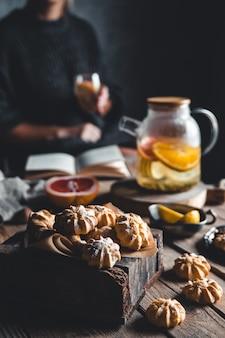 Vrouw leest en hete thee met verse grapefruit op houten tablet. gezonde drank, eco, veganistisch.