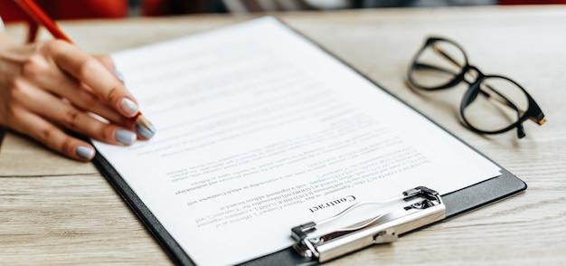 Vrouw leest en ondertekent documenten