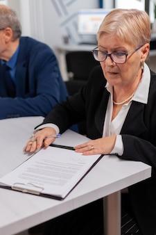 Vrouw leest financiële documenten in de vergaderruimte voordat ze deze ondertekent