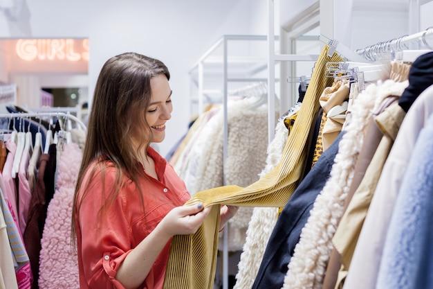 Vrouw leest het etiket en koopt rode trui in winkelcentrum