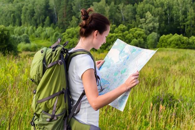 Vrouw leest kaart op wandeltocht. jonge vrouw die een reis met een kaart in openlucht plant