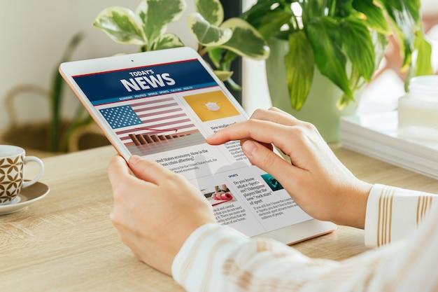 Vrouw leest nieuws online op haar tablet vanuit de woonkamer