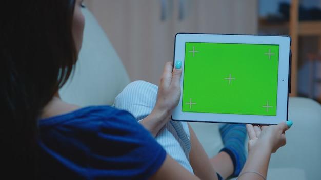 Vrouw leest op digitale tablet met groen schermachtergrond terwijl liggend op een gezellige bank. kijkend naar sjabloon chroma key geïsoleerde slimme notebook display met behulp van techology internet zittend op de bank.