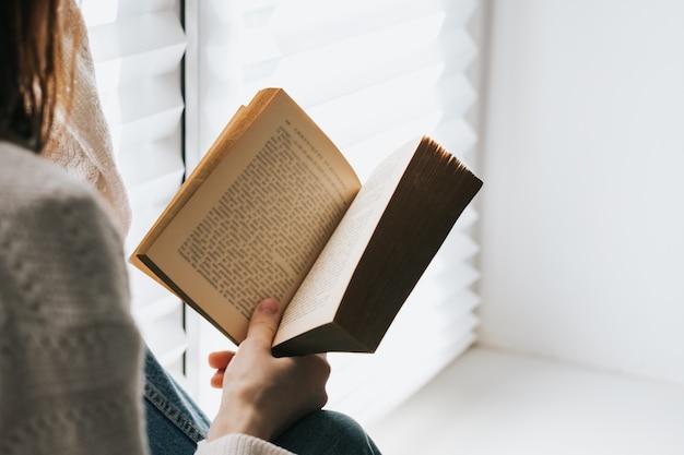 Vrouw leest overdag thuis een boek bij het raam.