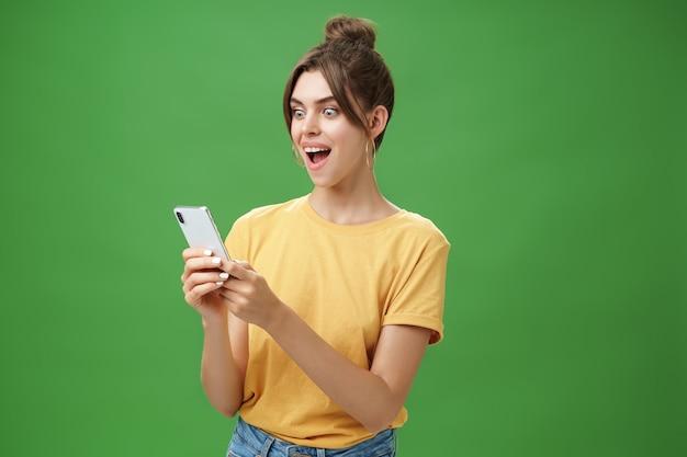 Vrouw leest verrassend bevredigend bericht in smartphone mond openen van opwinding