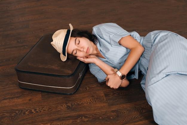 Vrouw legde haar hoofd op koffer en slaapt.