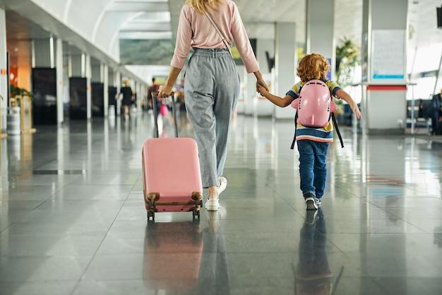 Vrouw leidt een kind door een luchthavenhal