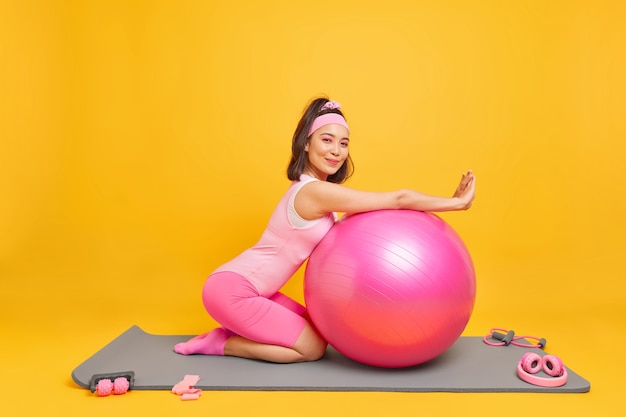 Vrouw lenas op fitness bal heeft tevreden uitdrukking gekleed in activewear neemt pauze na training thuis houdt van gymnastiek en aerobics poses op mat binnen