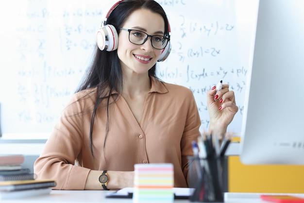 Vrouw leraar in koptelefoon kijken naar computerscherm