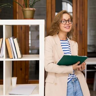 Vrouw leraar met notitieboekje in de klas