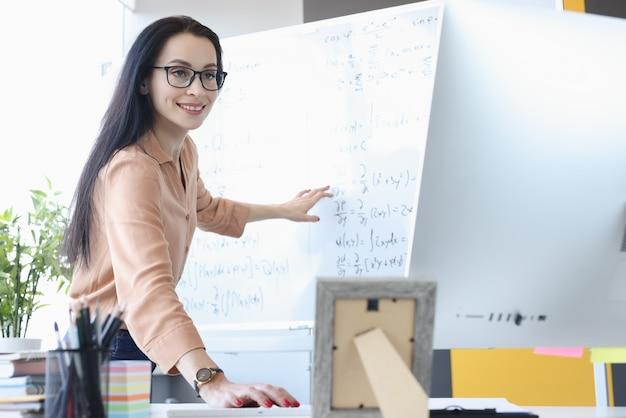 Vrouw leraar wiskundige formules in computerscherm tonen