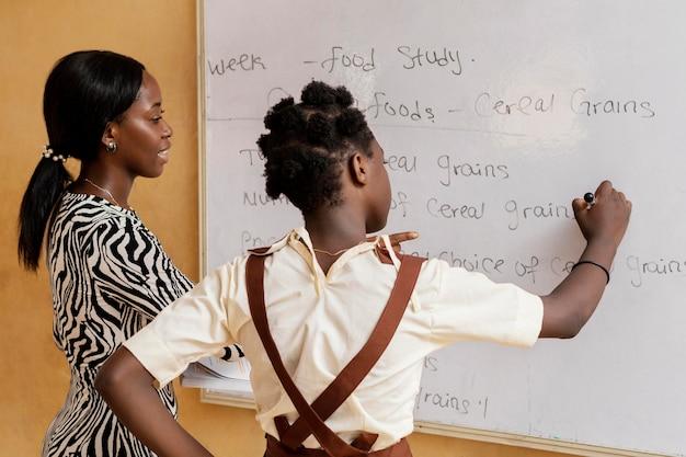 Vrouw lesgeven aan kinderen in de klas