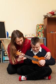 Vrouw lesgeven jongen met down syndroom om gitaar te spelen