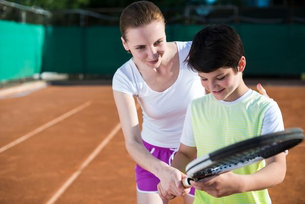 Vrouw lesgeven kind over tennis