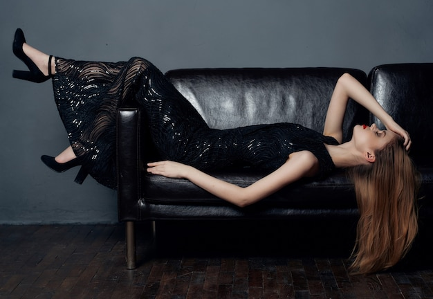 Vrouw leunend op de bank in een zwarte jurk