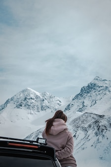 Vrouw leunend op een zwart voertuig voor verbazingwekkende besneeuwde en rotsachtige bergen en bewolkte luchten