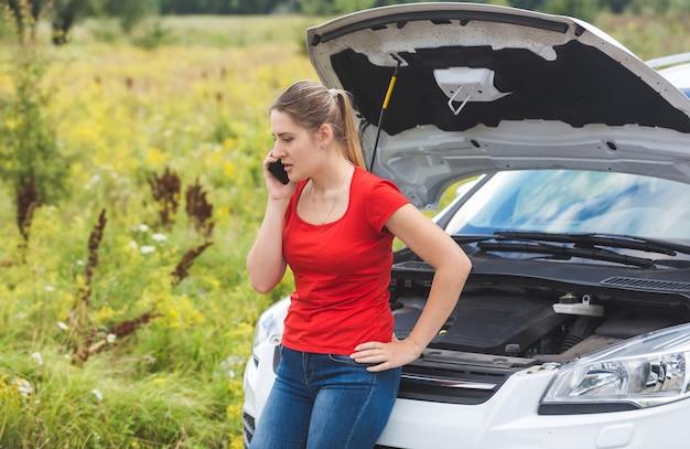 Vrouw leunend op kapotte auto en bellen om hulp via mobiele telefoon