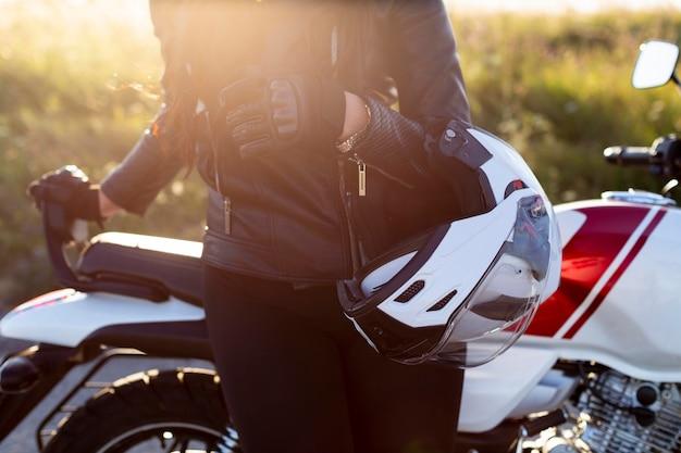 Vrouw leunend tegen haar motorfiets terwijl ze helm vasthoudt