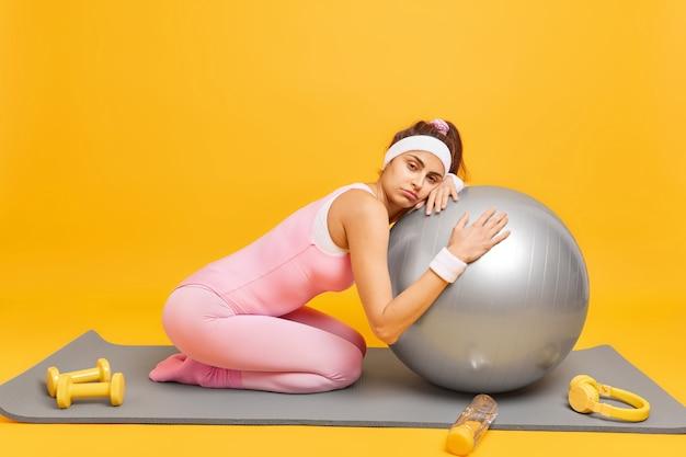 Vrouw leunt op fitnessbal voelt vermoeidheid na aërobe training draagt hoofdband polsband en activewear poses op karemat geïsoleerd op geel