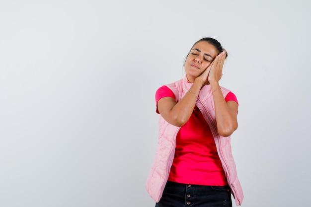 Vrouw leunt op handpalmen als kussen in t-shirt, vest en ziet er slaperig uit