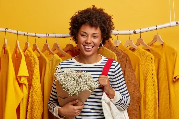 Vrouw levensstijl, mode, consumentisme concept. afro-amerikaanse vrouw met blij gezicht expressie, staat in kledingwinkel, draagt boodschappentas op schouder, krijgt bloemen van echtgenoot, gele achtergrond