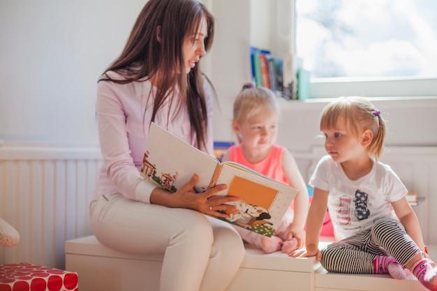 Vrouw lezend boek aan meisje