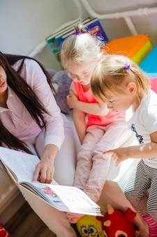 Vrouw lezend boek voor kinderen