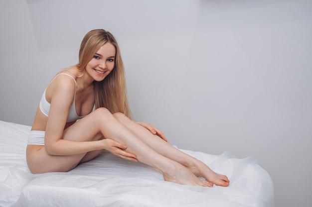 Vrouw lichaamsverzorging mooie blonde vrouw met lange gebruinde benen met perfecte gladde zachte huid pedicure