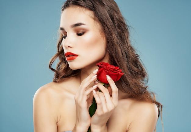 Vrouw lichte make-up roos in de hand luxe blauwe achtergrond